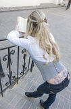 Portrait of Caucasian Blond Female With Book Standing on Stairs Outdoors and Reading. Huge Flowery Tattoo on Back. Vertical Image Composition stock photos