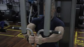 The portrait of caucasian bodybuilder who is finishing his effort in chest muscules training in the gym. The man is sitting on the machine, holding handles and stock footage