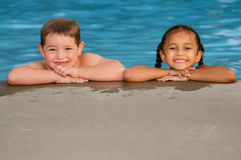 Portrait of Caucasian boy and mixed race girl in pool Stock Photo