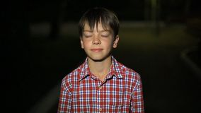 Portrait of a Caucasian boy in a plaid shirt at night in the city. close-up face. Portrait of Caucasian boy in a plaid shirt at night in the city. close-up face stock video