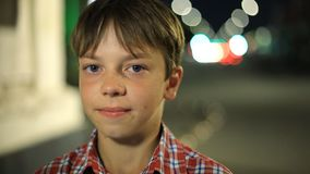 Portrait of a Caucasian boy in a plaid shirt at night in the city. close-up face. Portrait of Caucasian boy in a plaid shirt at night in the city. close-up face stock footage
