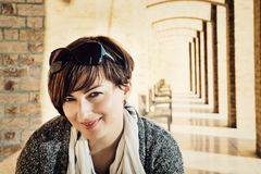 Portrait of caucasian brunette in front of the ancient corridor Royalty Free Stock Photography