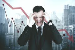 Stressful businessman with declining finance chart royalty free stock photography