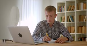 Portrait of caucasian businessman typing on laptop attentively and making notes being busy on bookshelves background. Portrait of caucasian businessman typing stock video