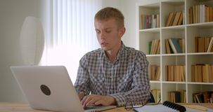Portrait of caucasian businessman working with laptop turns to camera and watches calmly on bookshelves background. Portrait of caucasian businessman working stock footage