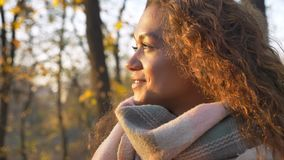 Portrait of caucasian curly-haired woman smilingly watching into camera and turning to sun on autumnal park background.