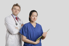 Portrait of a Caucasian doctor standing with an Asian nurse over gray background Stock Photos