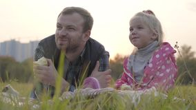 Portrait of caucasian father and his little blonde daughter sitting on the meadow and eating apples. Little girl in. Dotted pink jacket and adult caucasian man stock footage
