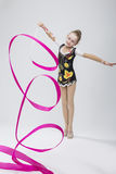 Portrait of Caucasian Female Rhythmic Gymnast. In Professional Competitive Suit Doing Artistic Ribbon Spirals Exercises in Studio On White. Vertical Composition stock images