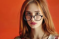 Portrait of a caucasian female young model in glasses in an ivo. Ry dress. Conceptual studio photo isolated on the red background royalty free stock images