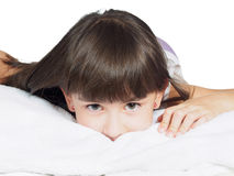 Portrait of caucasian funny girl child kid on the bed isolated Royalty Free Stock Images