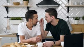 Portrait of caucasian gay couple are sitting behind kitchen table and having breakfast in the morning at kitchen. Handsome young guy is feeding his partner stock video footage