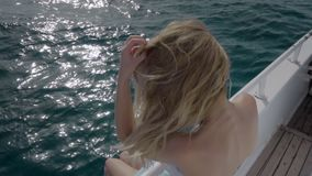 Portrait of Caucasian girl in bikini and sunglasses on the deck of an ocean yacht in the sea. He plays with the hair in. The wind. The concept of freedom, leave stock video footage