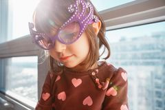 Portrait of Caucasian girl chil with funny glasses. Sitting on window sill at home celebrating birthday. Toddler preschooler wearing funny glasses, playing stock photos