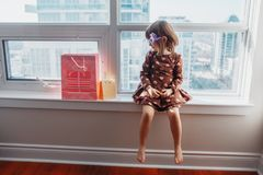 Girl child sitting on window sill at home opening birthday gifts. Portrait of Caucasian girl child sitting on window sill at home with birthday gifts, present stock photo