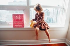 Girl child sitting on window sill at home opening birthday gifts. Portrait of Caucasian girl child sitting on window sill at home opening birthday gifts, present royalty free stock photos