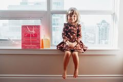 Girl child sitting on window sill at home opening birthday gifts. Portrait of Caucasian girl child sitting on window sill at home opening birthday gifts, present royalty free stock images