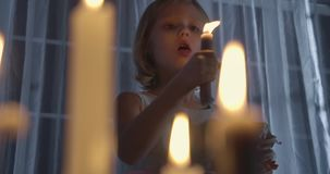 Portrait of Caucasian girl holding doll and blowing out candle. Weird child standing in candlelight in front of big