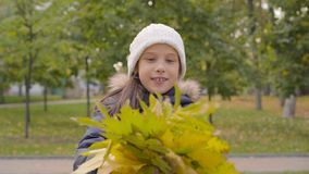Portrait of a caucasian girl in white hat holding a bunch of yellow leaves and smiling. Pretty young lady enjoying. Autumn day in the park stock footage