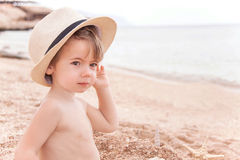 Portrait of caucasian happy baby (boy) in the hat at the beach. Stock Image