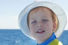 Portrait of caucasian happy baby boy in the hat. Child is smiling in summer day at the beach. Kid is enjoying ocean. Image has copyspace for text. Outdoor stock photo