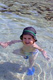 Portrait of Caucasian happy baby boy in sea with hat Stock Photo