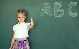 Portrait of caucasian happy child girl with. School chalkboard or blackboard background. Education concept. Portrait of caucasian happy child girl. School Stock Image