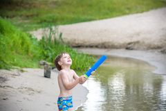 Portrait of caucasian little boy in straw hat playing toys and water pump on the beach. royalty free stock images