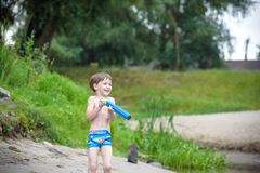 Portrait of caucasian little boy in straw hat playing toys and water pump on the beach. stock images
