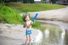 Portrait of caucasian little boy in straw hat playing toys and water pump on the beach. royalty free stock photos
