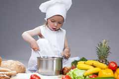 Portrait of Caucasian Little Girl In Cook Uniform Working With Scoop Royalty Free Stock Photo