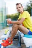 Portrait of caucasian male runner in headphones sitting on sport stadium Royalty Free Stock Image