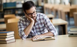 Portrait of caucasian male student sitting at the desk. Behind stack of books looking exhausted and tired to study Royalty Free Stock Photo