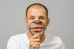 Portrait of caucasian man with magnifier makes fun face. Magnifier to the mouth royalty free stock image