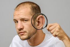 Portrait of caucasian man with magnifier makes fun face. Magnifier to the ear stock images