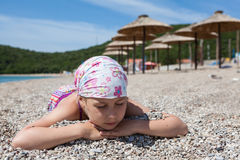 Portrait of Caucasian pretty girl sleeping on sand in swimwear and scarf on head. Seashore with parasols Royalty Free Stock Image