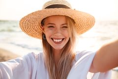 Portrait of caucasian pretty woman 20s in summer straw hat smili. Ng and taking selfie while walking at seaside Stock Images