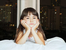Portrait of caucasian sad girl child kid on background window at night Stock Photos
