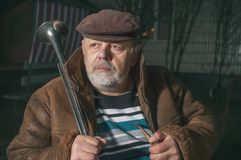 Caucasian senior man sitting next to his house with horn at cold autumn night Stock Image