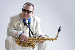 Portrait of Caucasian Smiling Man Posing With Saxophone and Wearing Sunglasses. Stock Photo