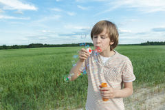 Portrait of Caucasian teenager boy with floating soap bubbles on dusty dirt farm field road Royalty Free Stock Images