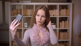 Portrait of caucasian wavy-haired blonde teacher making seductive selfie photos into camera at library. Portrait of caucasian wavy-haired blonde teacher making stock video footage