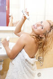 Portrait of Caucasian Woman in Bathroom Cleaning Her Teeth with Electric Toothbrush Indoors. Stock Image