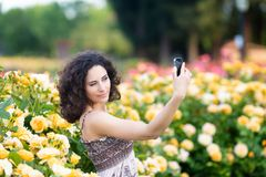 A portrait of Caucasian woman with dark curly hair taking selfie near yellow rose bushes in a rose garden royalty free stock photo