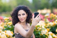 A portrait of Caucasian woman with dark curly hair taking selfie near yellow rose bushes in a rose garden royalty free stock images