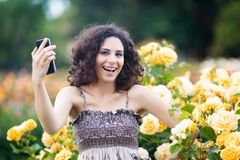 A portrait of Caucasian woman with dark curly hair taking selfie near yellow rose bushes in a rose garden, video call, chat, smile stock image