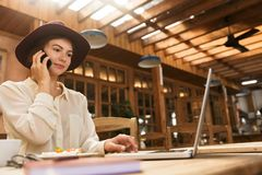 Portrait of caucasian woman wearing hat speaking on smartphone while working on laptop stock image