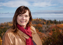 Portrait of a Caucasian Woman Wearing a Tan Leather Jacket and Red Scarf with a Scenic Fall Color and Ocean Background Stock Image