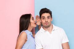 Portrait of caucasian woman whispering secret or interesting gossip to curious man in his ear, isolated over colorful background. Portrait of caucasian women stock photos
