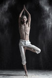 Portrait of caucasian young man wearing white sport pants doing yoga or pilates exercise. royalty free stock image